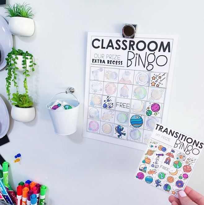 Classroom Management Bingo on whiteboard with a woman holding a desk size transitions bingo next to the large version